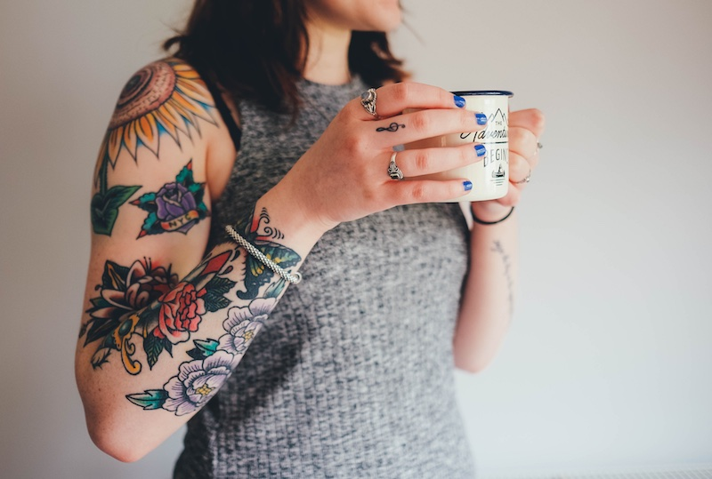 Tattooed woman holding a cup